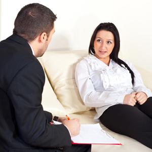 Patient woman talking with psychologist man