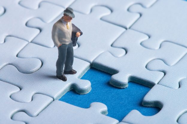 plastic figure standing in front of a hole in a puzzle